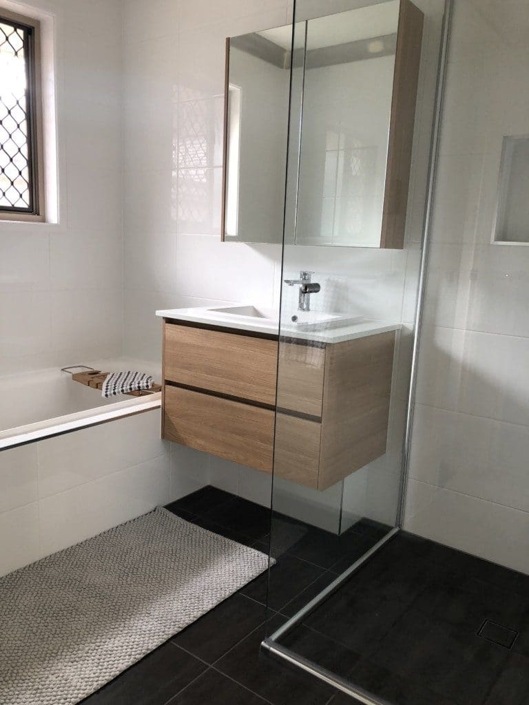 Black and white tiles, clear glass, shaving cabinet, mirror, wash basin, tub, shower, storage